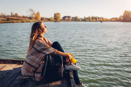 Traveler with backpack relaxing by autumn river at sunset. Young woman sitting on pier breathing free feeling happy. Active lifestyle