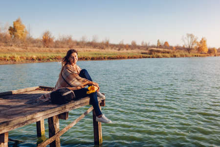 Traveler girl with backpack relaxing by autumn river at sunset. Young woman sitting on pier admiring landscape and fall weather. Active lifestyle
