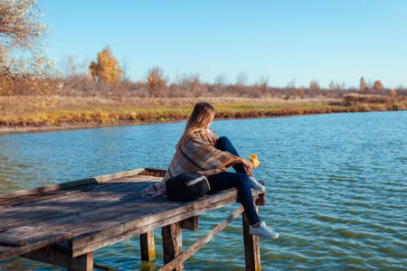 Traveler with backpack relaxing by autumn river at sunset holding leaves. Young woman sitting on pier admiring landscape and weather. Active lifestyle 免版税图像