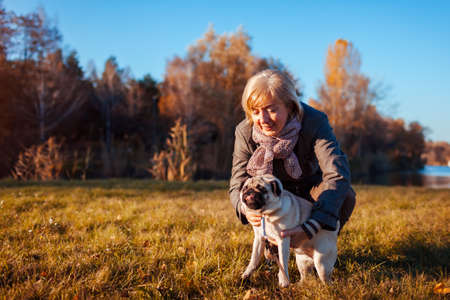 Walking pug dog in autumn park by river. Happy woman hugging pet and having fun with best friend outdoors.