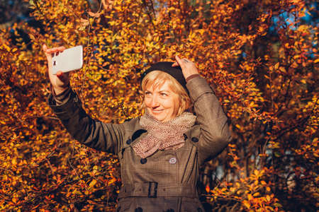 Middle-aged woman taking selfie on phone walking in park. Stylish senior lady having fun in autumn forest