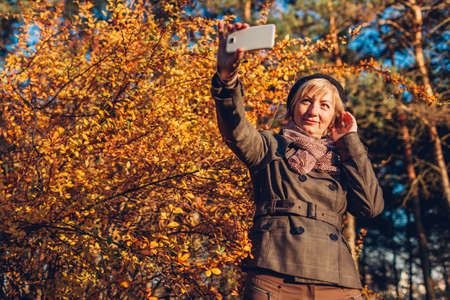 Middle-aged woman taking selfie on smartphone walking in fall park. Senior lady taking photos of herself in autumn forest by yellow trees