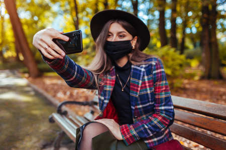 Woman wears mask in park during coronavirus covid-19 pandemic. Girl taking selfie on smartphone. Stay safe. Autumn fashion 免版税图像