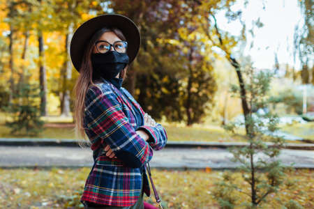 Stylish woman wears protective mask outdoors during coronavirus covid-19 pandemic. Girl walking in autumn park