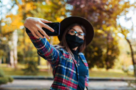 Stylish young woman wears mask in park during coronavirus covid-19 pandemic. Girl taking selfie on smartphone.