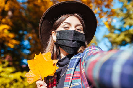 Portrait of woman wearing mask in fall park during coronavirus covid-19 pandemic and taking selfie. Stylish autumn