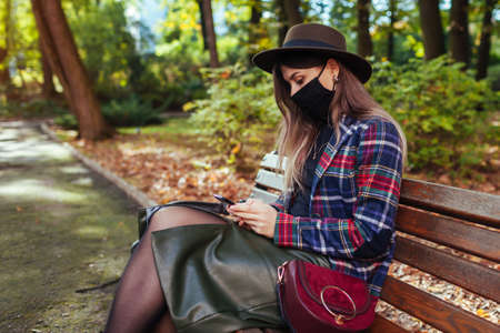 Woman wears mask in park during coronavirus covid-19 pandemic. Girl using phone relaxing on bench in autumn park