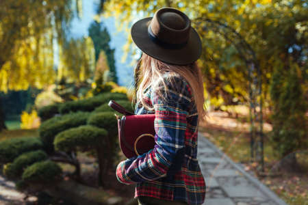 Portrait of young woman holding stylish burgundy purse in park. Autumn spring female clothes and accessories. Fashion