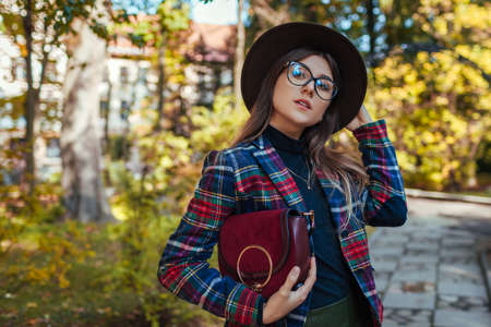 Woman holding stylish burgundy handbag in park. Autumn spring female clothes and accessories. Fashion