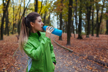 Runner having rest after workout in autumn park. Woman drinking water. Sportive active lifestyle