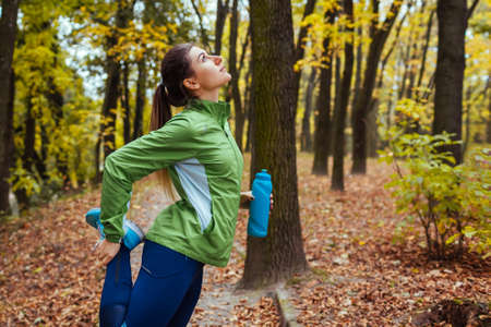 Training and exercising after run in autumn park. Woman stretching legs outdoors. Active healthy lifestyle