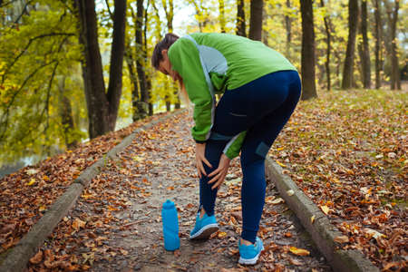 Young runner injured leg during workout exercises in autumn park. Woman feels ankle pain and crick. Body sore