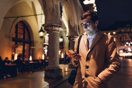 Young handsome man using smartphone at night on Market square in Krakow Poland. Traveler checking news social media.
