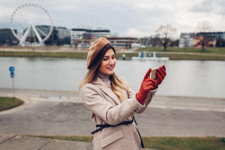 Stylish woman taking selfie on phone walking along pier by Wisla river in Krakow, Poland enjoying landscape.