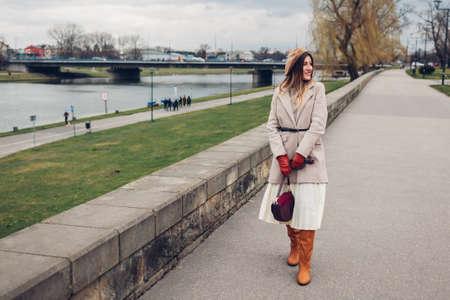 Stylish woman tourist walking along pier by Wisla river in Krakow, Poland enjoying landscape. Europe spring trip