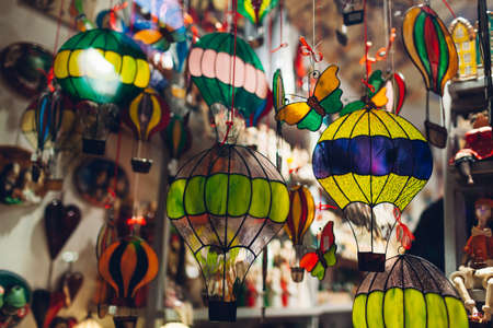 Showcase with murano glass figures in souvenir shop. Statues of air balloons hung on display