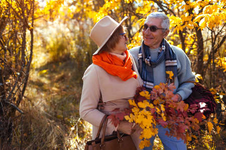 Senior family couple walking in autumn forest. Middle-aged man and woman carry basket for picnic
