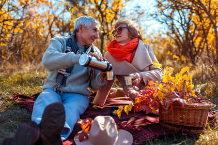 Senior family couple having tea   in fall forest. Happy man and woman enjoying picnic outdoors.