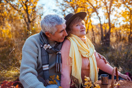 Senior family couple relaxing in autumn forest. Happy man and woman enjoying picnic and nature landscape