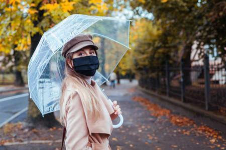 Portrait of young woman in protective mask walking along autumn city street under transparent umbrella during rain.