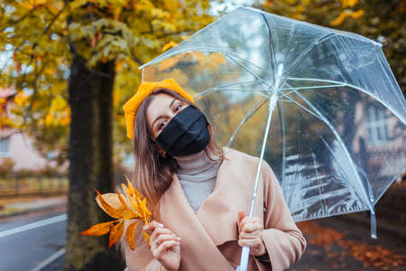 Stylish young woman in mask against covid walks on autumn street under transparent umbrella during rain with leaves.