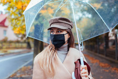 Young woman in protective mask walking along autumn city street under transparent umbrella during rain. Covid