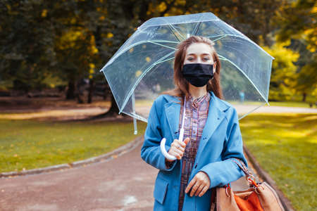 Stylish young woman in protective mask walking in autumn park under transparent umbrella after rain. Covid