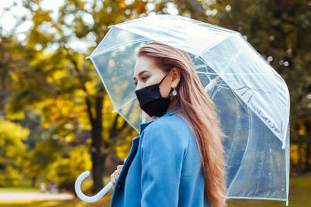 Close up of woman in protective mask walking in autumn park under transparent umbrella after rain. Covid 免版税图像