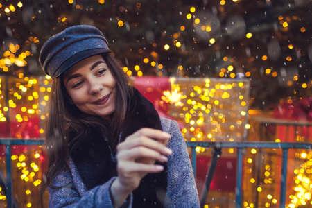 Christmas, New Year. Woman burning sparkler by Christmas tree on city street fair. Happy girl enjoys celebrating holidays and has fun 免版税图像
