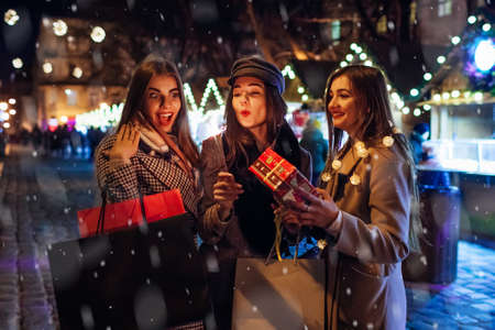New Year and Christmas. Women friends burning sparklers in Lviv on street fair having fun after shopping holding presents. Girls celebrating holidays under snow outdoors