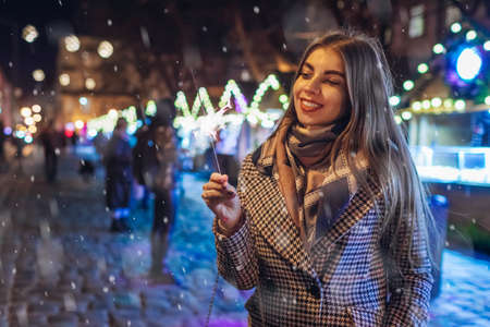 Christmas, New Year. Woman burning sparkler on city street fair in Lviv. Girl having fun outdoors. Celebrating winter holidays under snow
