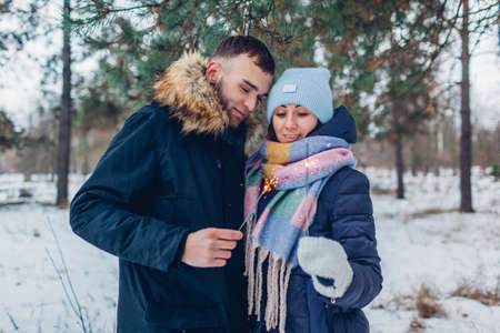 Young loving couple burning sparklers in snowy winter forest. Christmas and New year celebration. People having fun outdoors