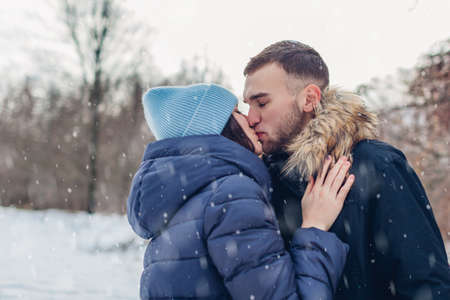 Boyfriend and girlfriend kissing outdoors walking and hugging in snowy winter park. Romantic date. Loving couple relax in forest 免版税图像