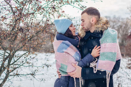 Man and woman walking and hugging in winter forest. People warming covered with blanket under falling snow. Seasonal activities 免版税图像