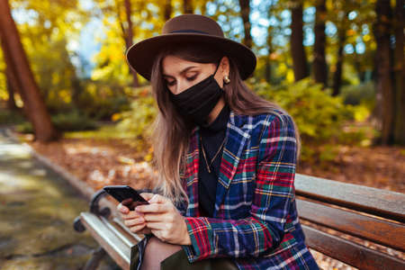 Woman wears mask in park during coronavirus covid-19 pandemic. Stylish girl using smartphone relaxing on bench in autumn park