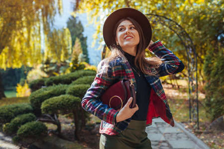 Pretty woman holding stylish burgundy handbag and wearing fall outfit in park. Autumn spring female clothes and accessories. Fashion