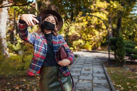 Stylish young woman wears protective mask in park during coronavirus covid-19 pandemic. Girl taking selfie on smartphone. Autumn fashion