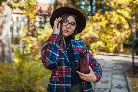 Portrait of woman holding stylish burgundy handbag and wearing hat in park. Autumn spring female clothes and accessories. Fashion