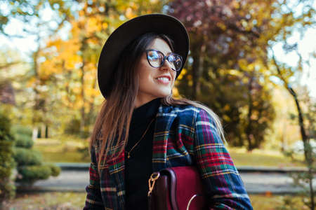Happy stylish woman walking in fall in park wearing hat, glasses and holding purse. Autumn spring female clothes and accessories. Fashion