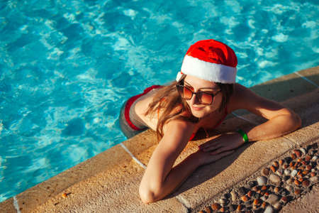 New Year and Christmas celebration. Woman in Santa's hat and bikini chilling in hotel swimming pool on resort. Tropical holiday vacation