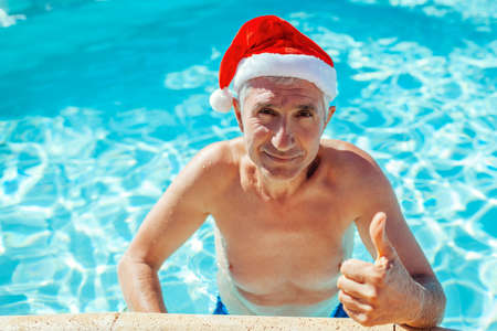 New Year and Christmas celebration. Senior man in Santa's hat shows thumb up relaxing in swimming pool. Tropical vacation 免版税图像