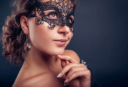 New year masquerade party. Beautiful young woman wearing black lace carnival mask and jewellery. Fashionable look. Standard-Bild