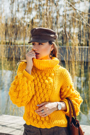 Woman wearing stylish yellow sweater and holding handbag in park. Spring fashion. Color of 2021 Фото со стока
