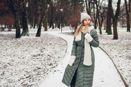 Winter fashion. Portrait of young woman wearing long green coat with scarf, hat, mittens in snowy park.