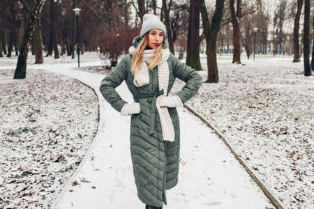 Winter female fashion. Young woman wearing long green coat with scarf, hat, mittens in snowy park. Фото со стока