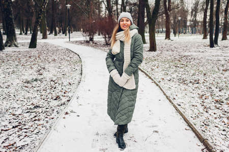 Winter fashion. Young woman wearing long green coat with scarf, hat, mittens and boots in snowy park. Фото со стока