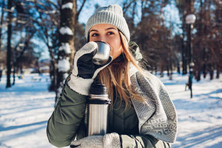 Woman drinking hot tea holding vacuum flask in winter park. Drinks to warm up in snowy frosty weather outdoors Фото со стока