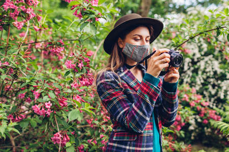 Woman photographer takes pictures of spring garden on digital camera wearing mask.