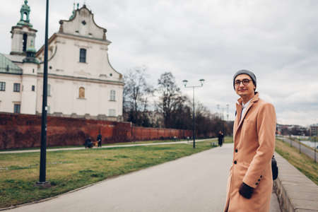 Tourist walking by church of St. Stanislaus Bishop by Wisla river in Krakow, Poland. Happy traveler man looking at camera