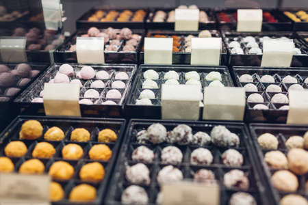 Assortment of chocolate colorful candies desserts on cafe showcase. Variety of sweets with different flavours nuts spices in store. Confectionery Фото со стока